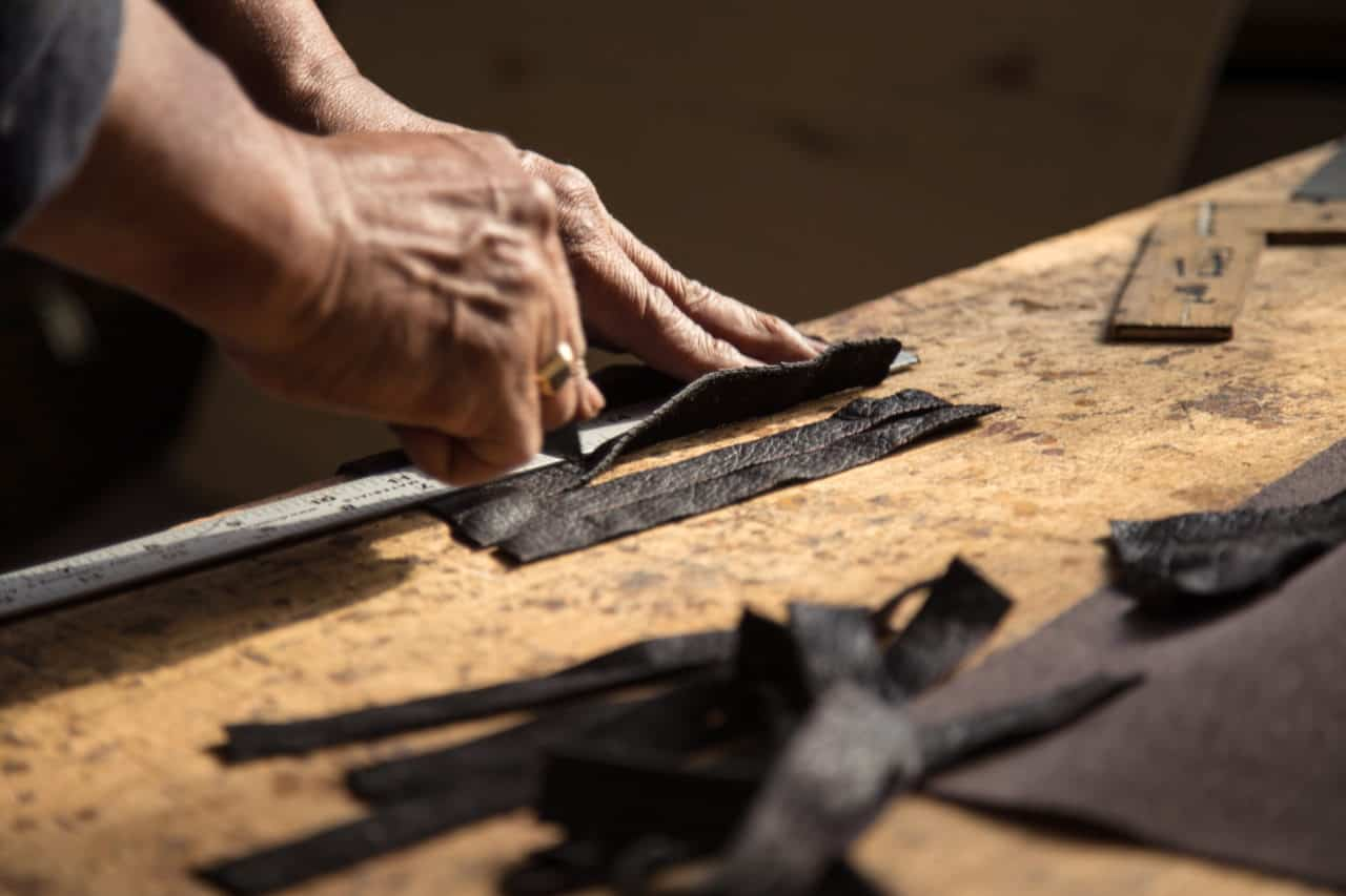 Hands cutting with a knife black custom luxury leather strips on table