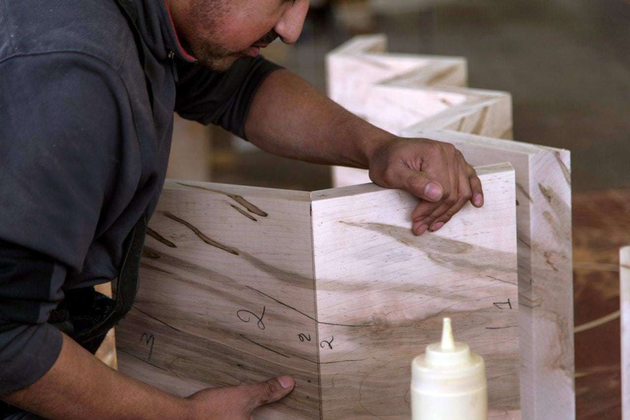 a man constructing the angle joints of a SENTIENT contemporary designed custom friends bookcase in luxury spalted maple