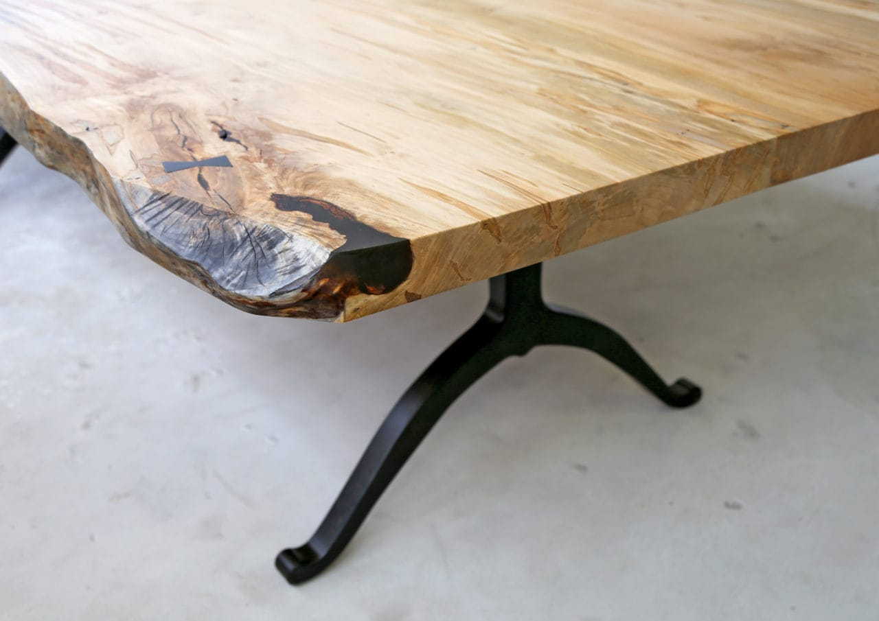 a corner detail of a SENTIENT contemporary designed light luxury maple custom live edge table with black wishbone legs