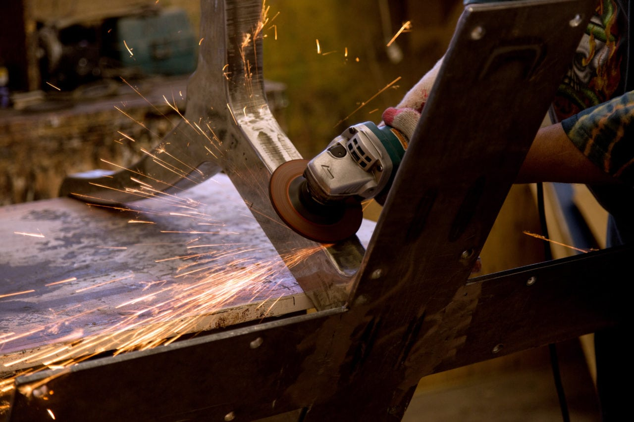 hand holding grinder on metal bar while red sparks fly