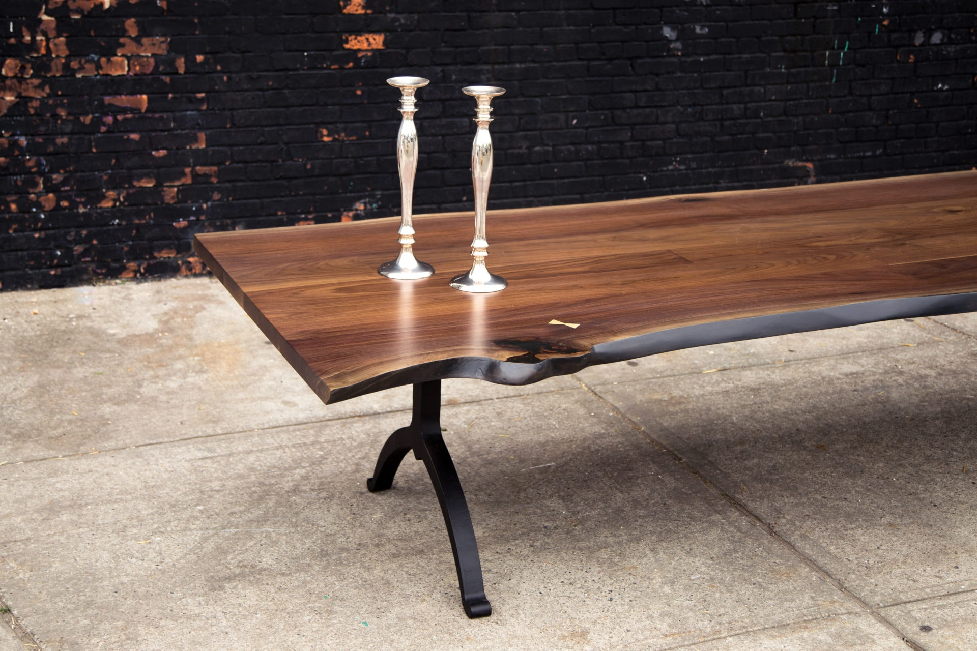 a SENTIENT American black walnut live edge table with blackened steel legs with two silver candlesticks on top