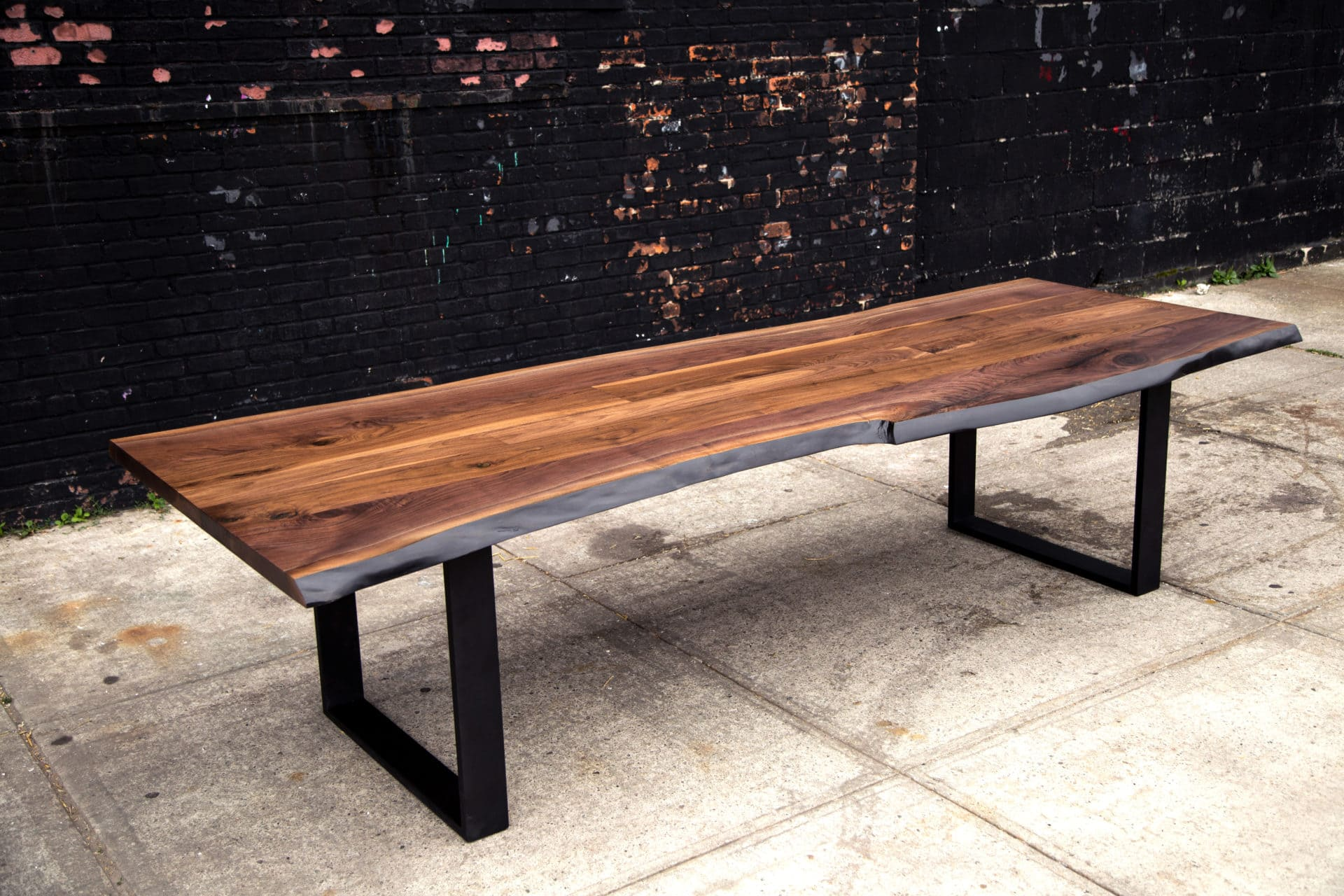 a SENTIENT contemporary designed custom walnut live edge luxury table with square blackened steel frame legs