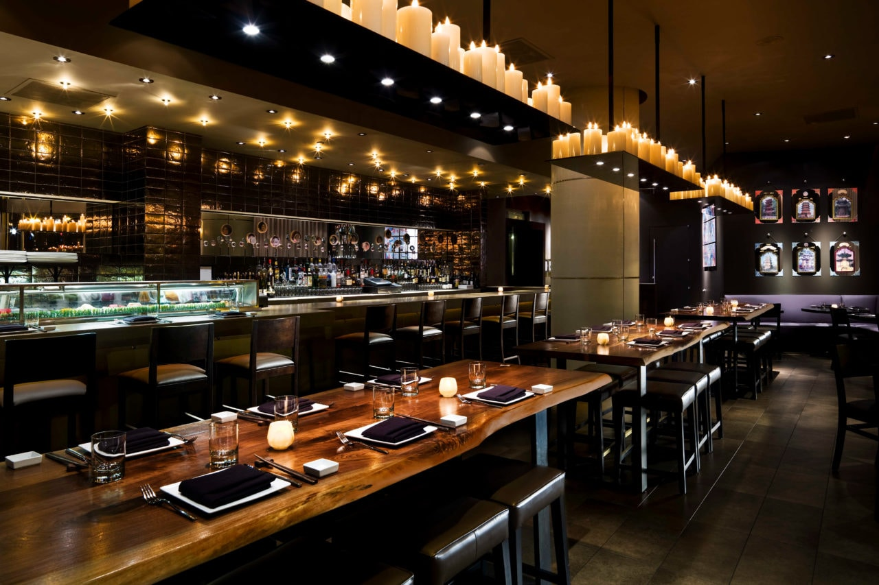 a SENTIENT contemporary designed walnut live edge custom bar top tables with upholstered bar stools at luxury Zentan restaurant