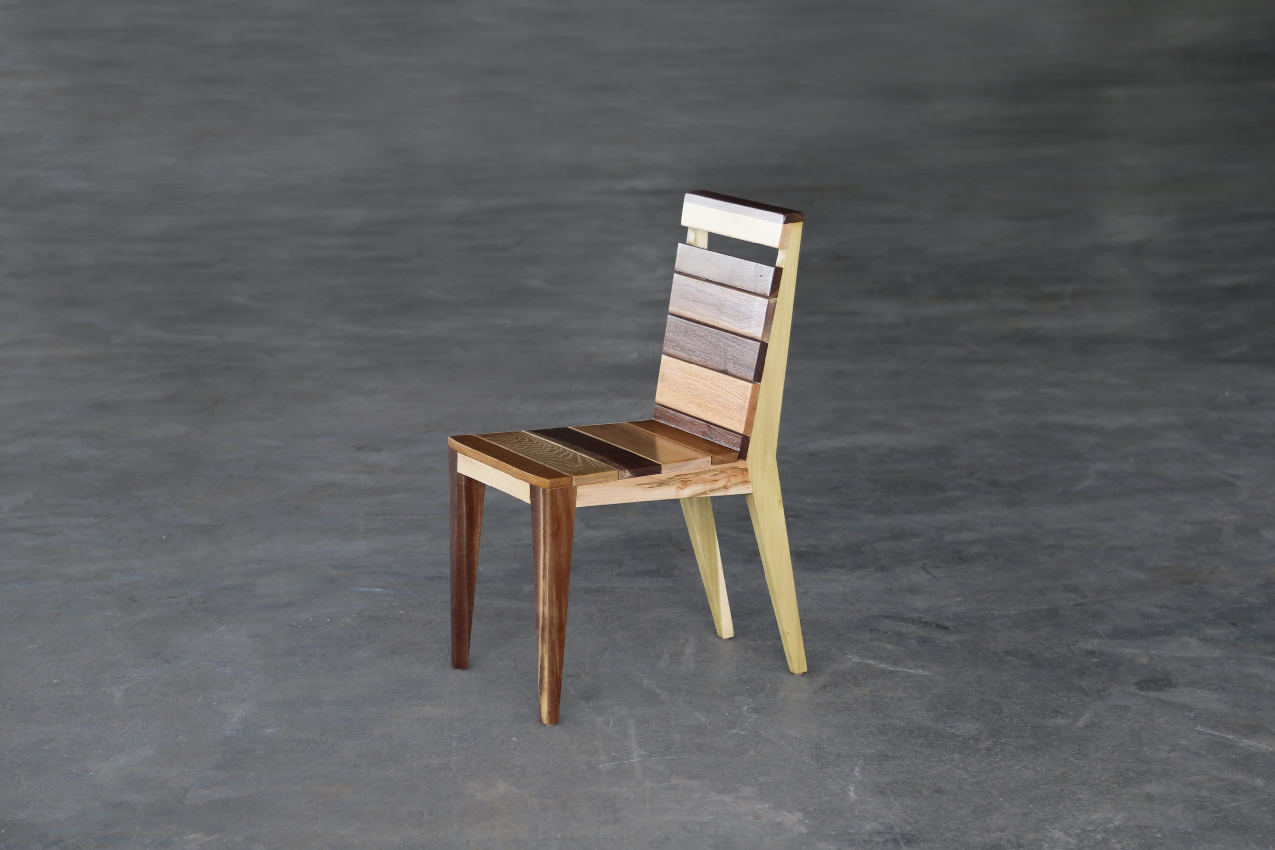 a SENTIENT contemporary designed Angles dining chair in walnut with custom stripped back and seat on a grey concrete floor