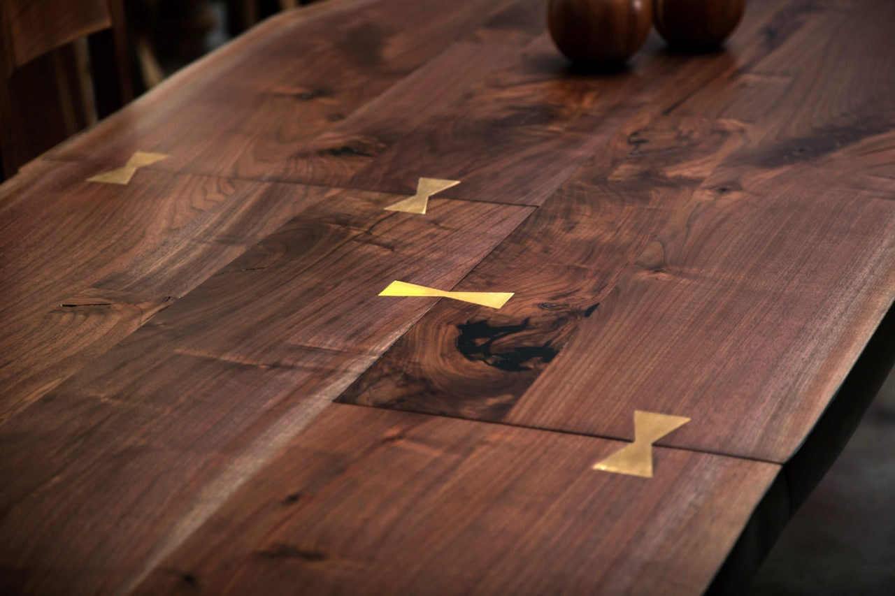 a live edge SENTIENT contemporary designed walnut custom table with multi butterfly inlaid joints