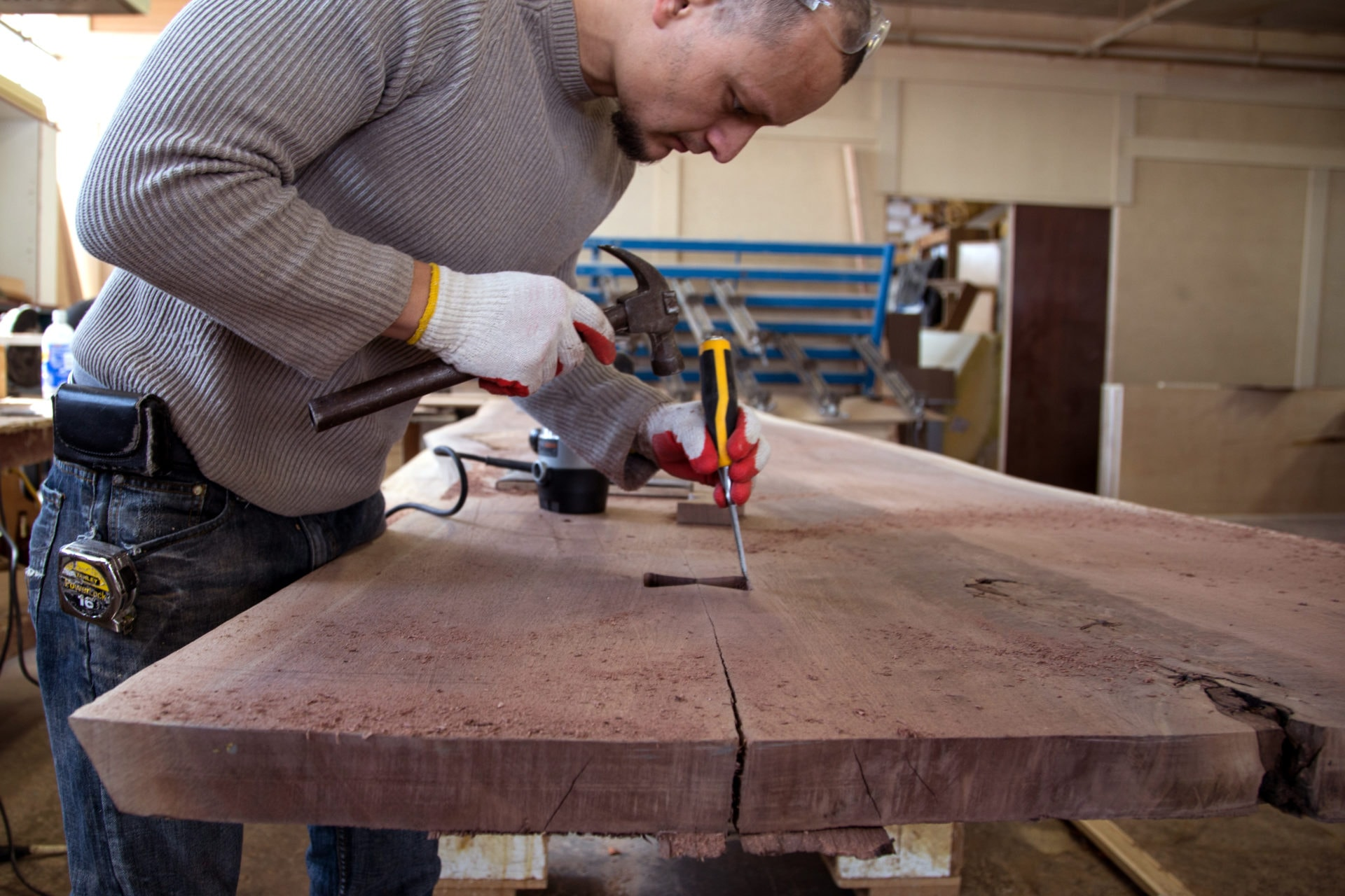 A person using tools to cut out a space for a butterfly joint into a solid luxury American black walnut wood live edge slab