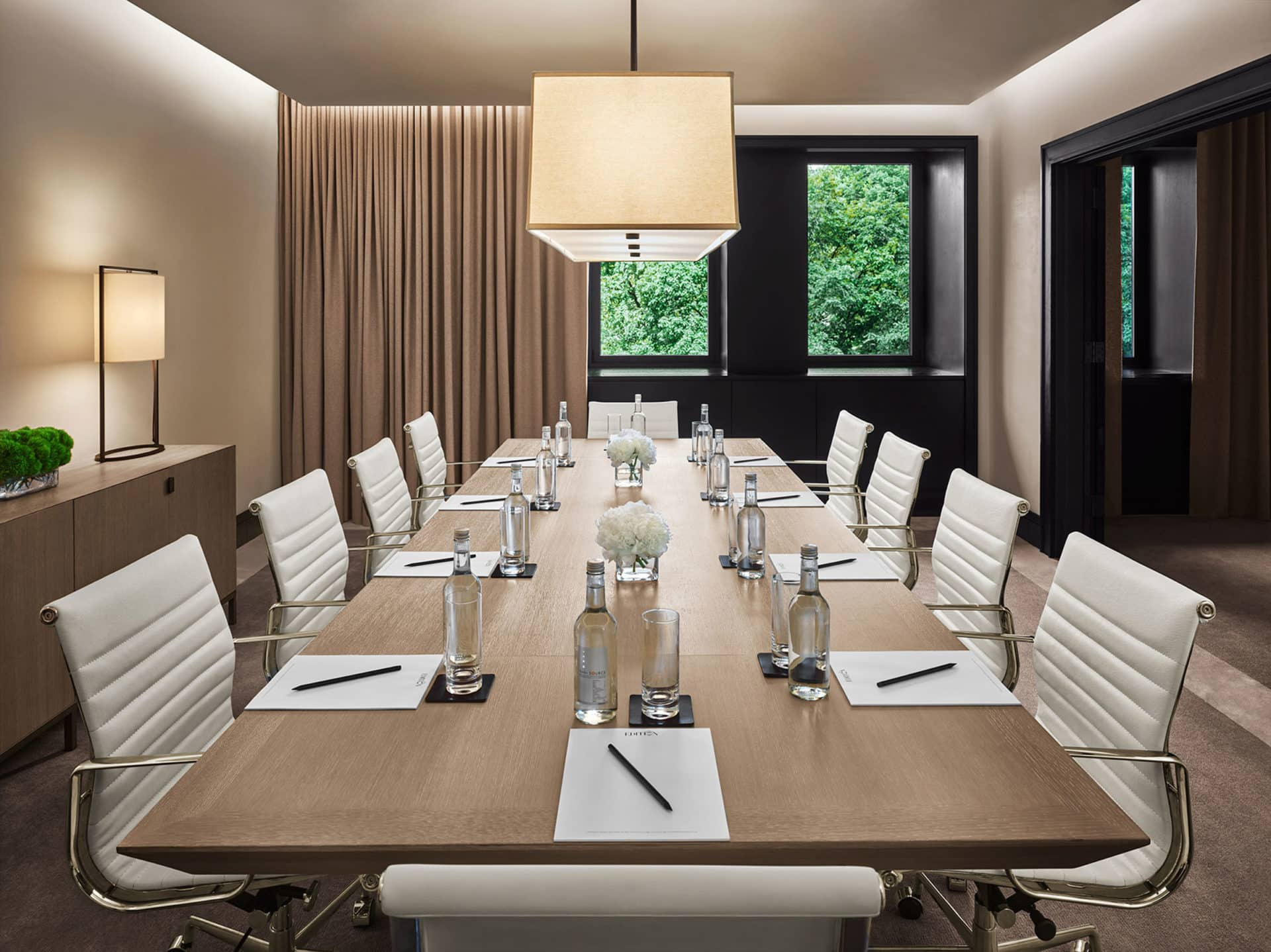 luxury conference table in walnut with white desk chairs