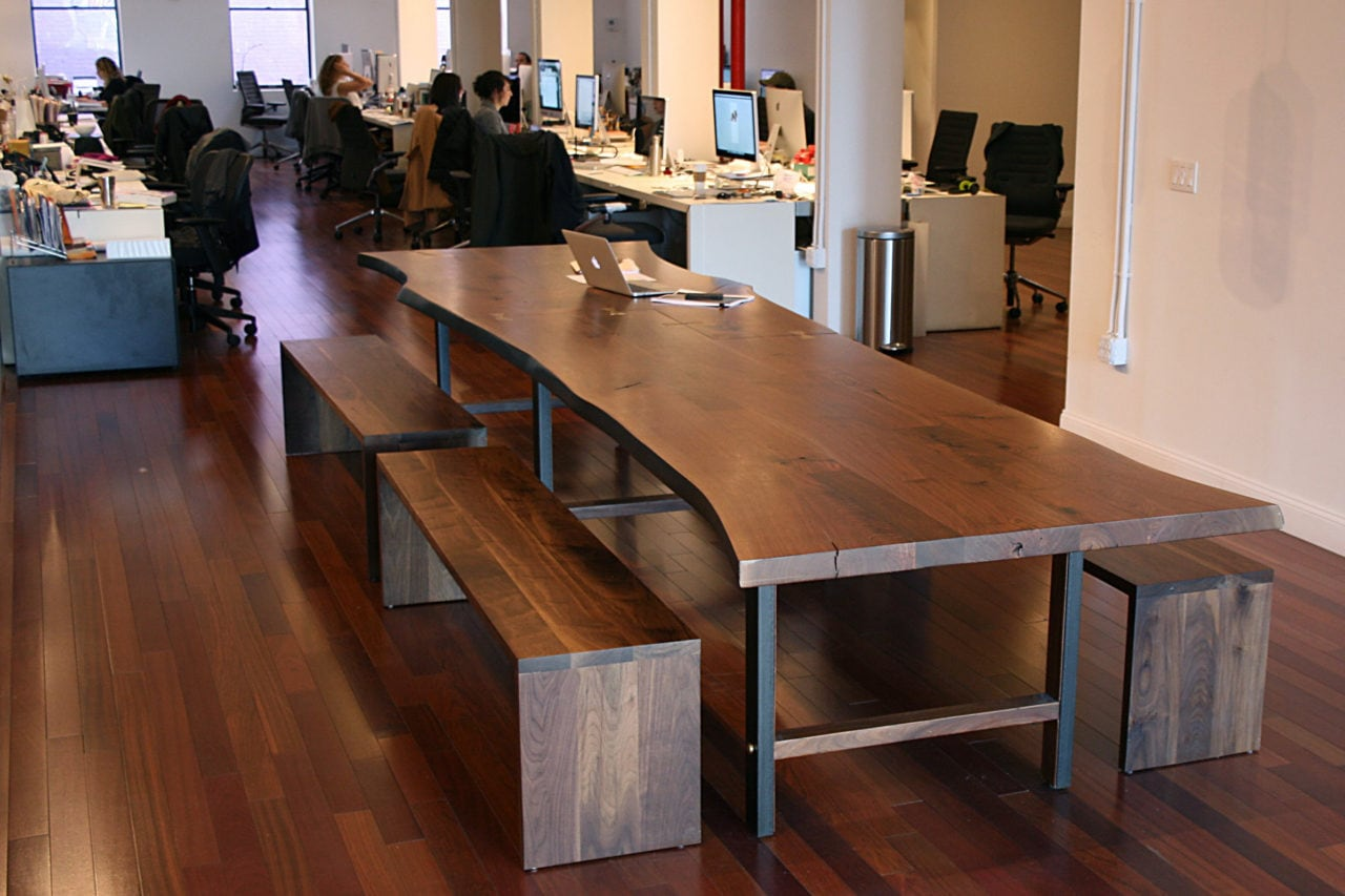 A SENTIENT contemporary live edge custom walnut table with benches in an open office setting