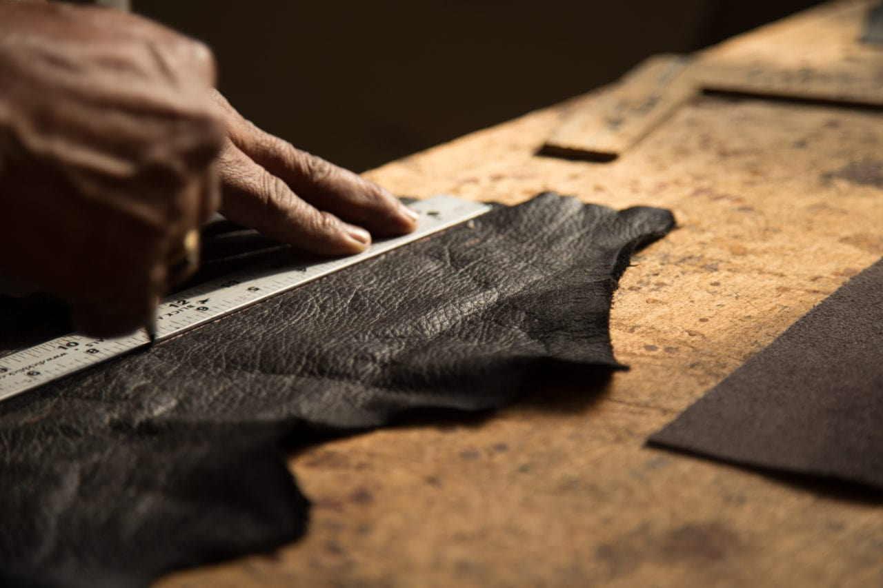 Hands cutting with a knife custom black textured luxury leather strips on table