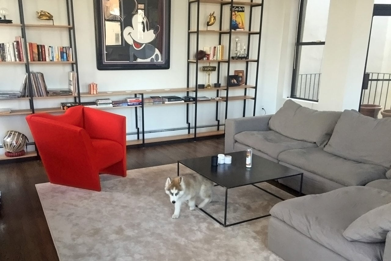 a SENTIENT contemporary designed nersi luxury red upholstered custom arm chair and furniture in living room setting
