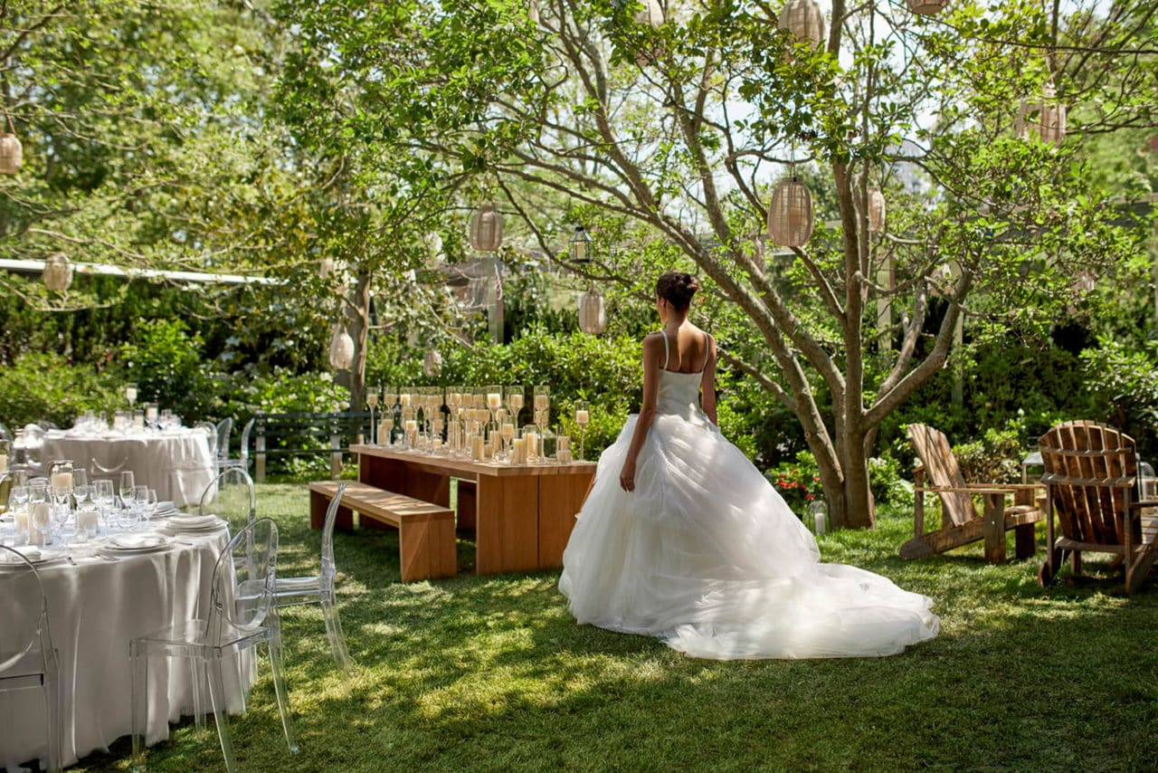 outdoor view with a woman in a wedding dress facing a SENTIENT contemporary communal table with candles and custom benches