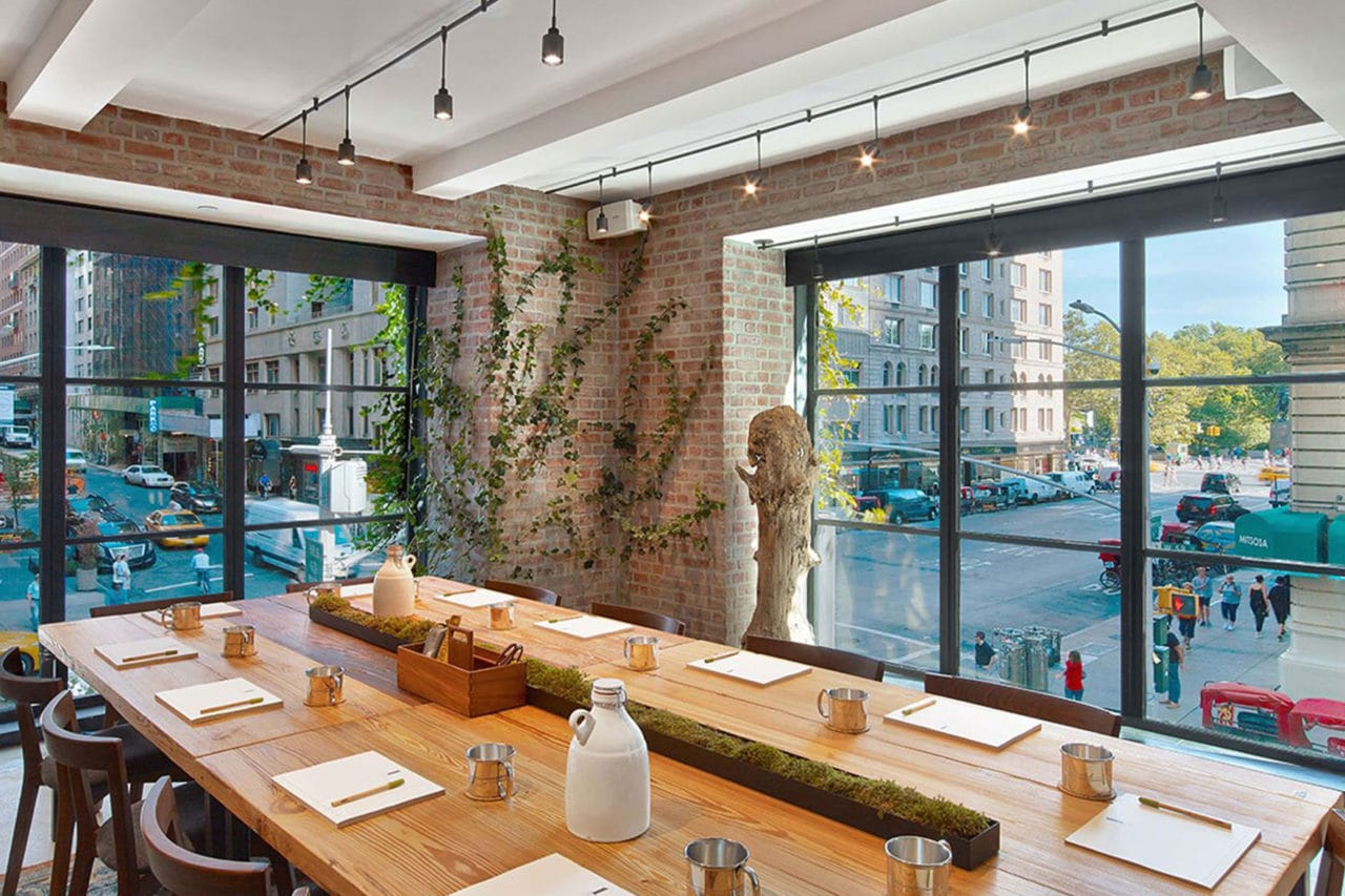 a wide custom SENTIENT contemporary designed maple table in a corner window view at luxury jams restaurant with brick walls