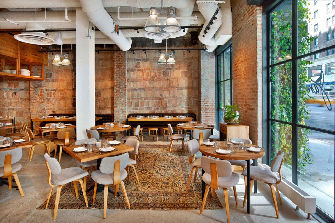 a cluster of SENTIENT contemporary designed custom wood tables and luxury upholstered chairs in jams restaurant