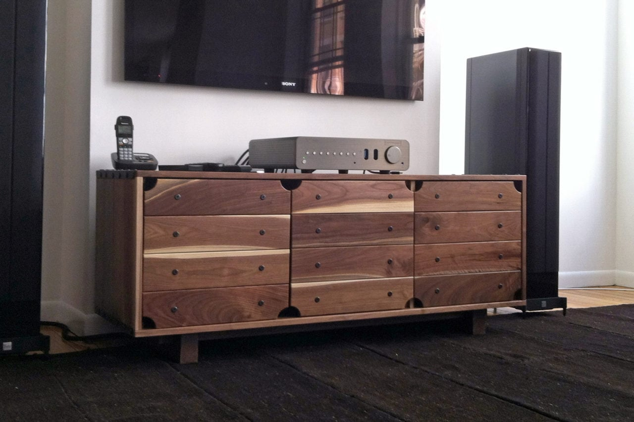 a SENTIENT contemporary designed custom red river credenza in walnut with stereo and phone equipment on top
