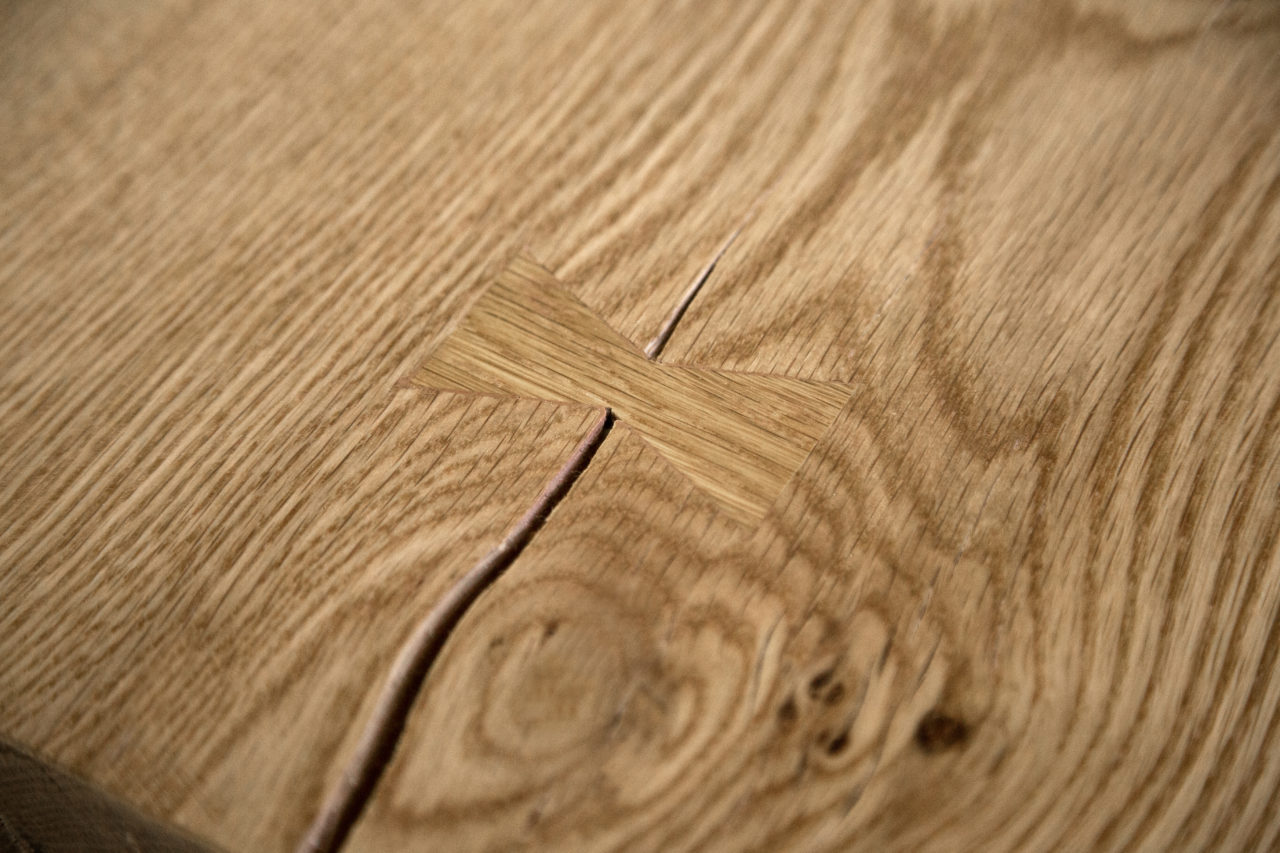 a detail view of a SENTIENT contemporary designed communal table in maple wood with custom butterfly joint and crack