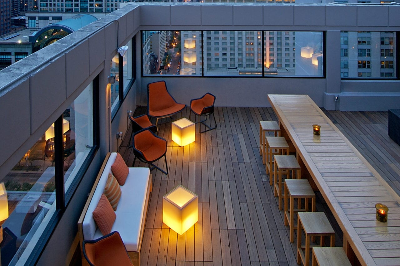arial view of a long SENTIENT contemporary designed communal custom wood table at the Stewart hotel affinia rooftop lounge