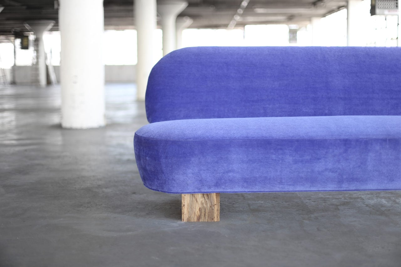 a half detail view of a SENTIENT contemporary designed custom sofa in luxury blue velvet with wood beam leg