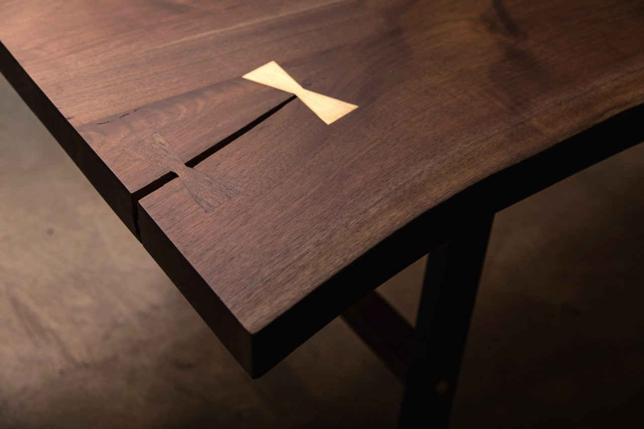 a luxury live edge SENTIENT contemporary designed custom table with brass butterfly inset at crack