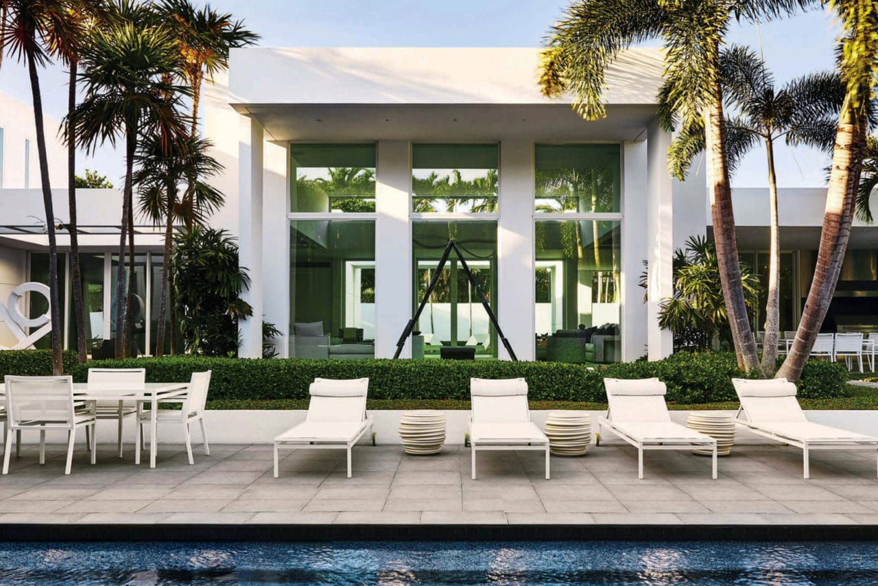 a luxury poolside view of a home with lounge chairs featuring SENTIENT contemporary designed custom furniture