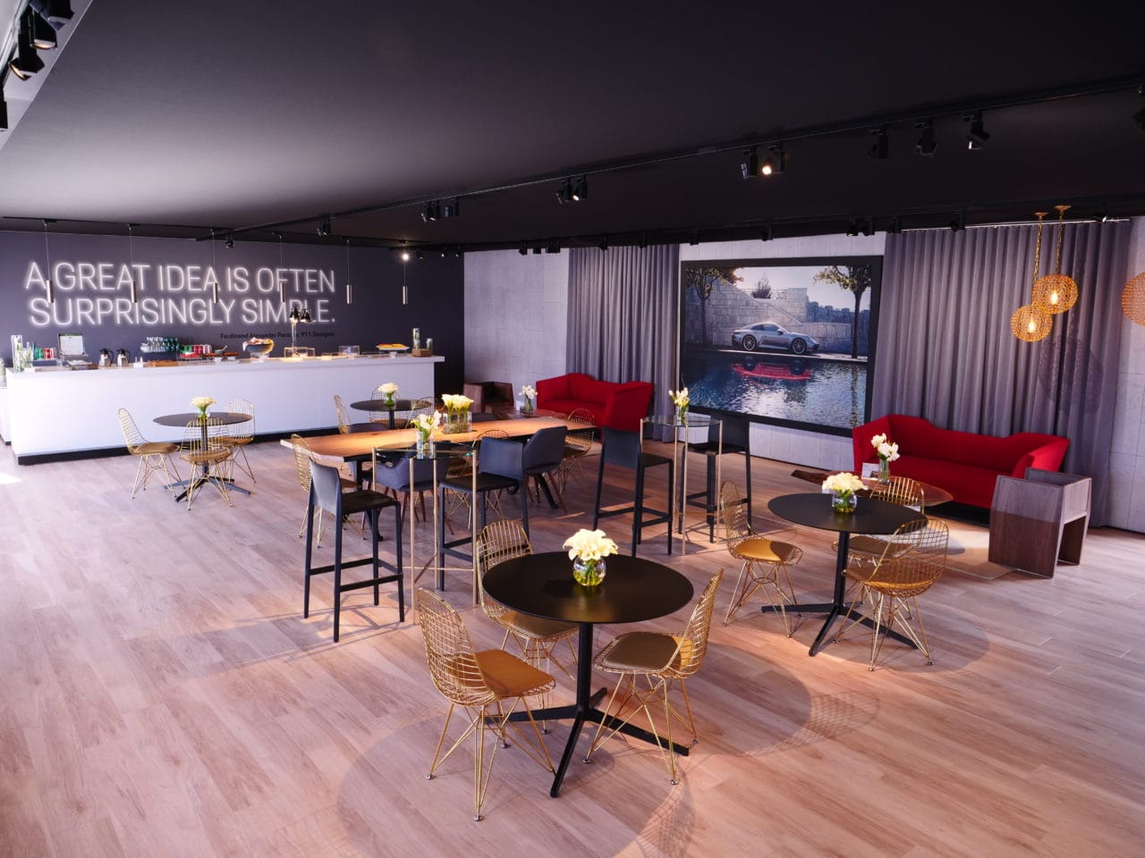 a SENTIENT contemporary designed walnut live edge table and furniture in porsche car show exhibition cafe