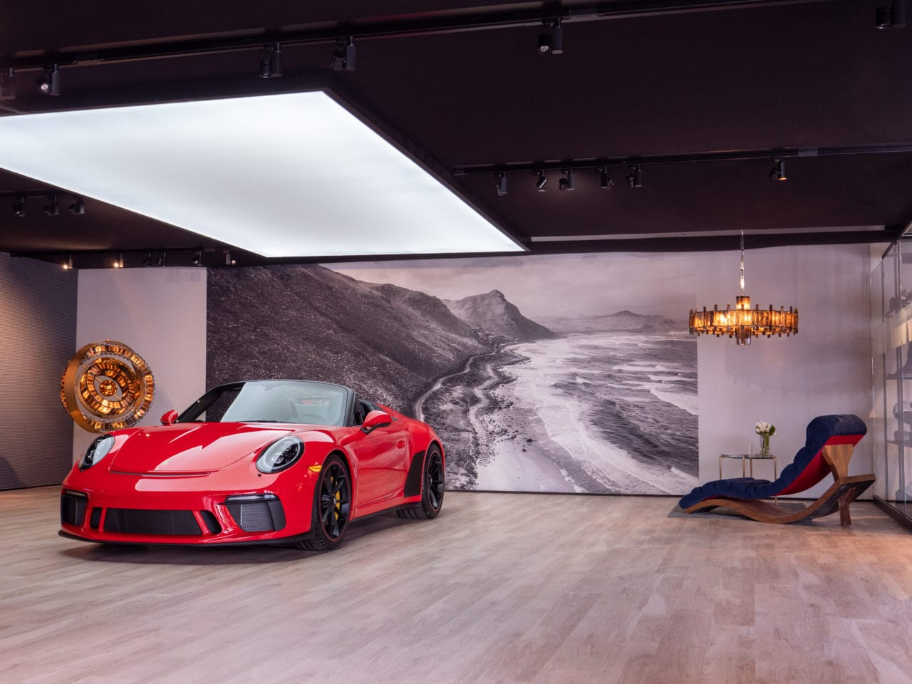 Red Porsche in car exhibition room with luxury blue SENTIENT Wave contemporary custom chair and landscape mural