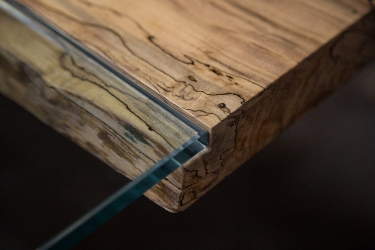 a SENTIENT contemporary designed Colorado table in ambrosia maple with custom glass inset detail view
