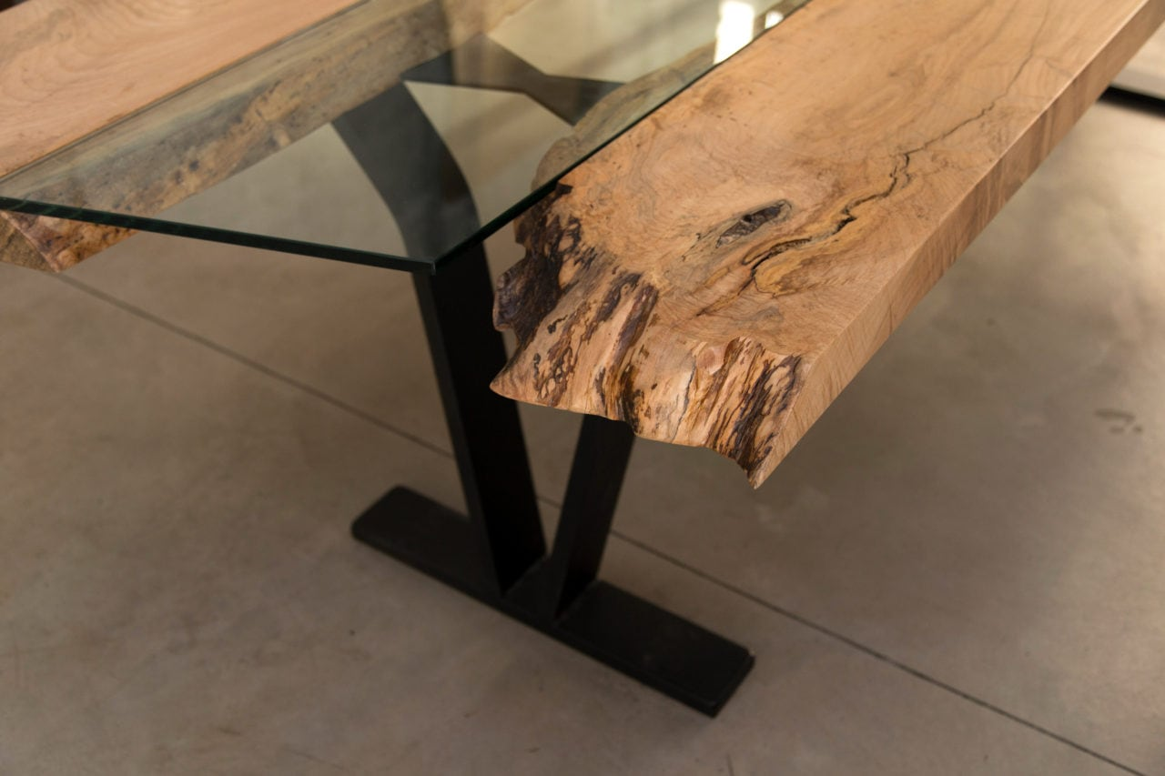 a SENTIENT contemporary designed Colorado table in maple with custom glass inset and blackened steel v shape leg detail view