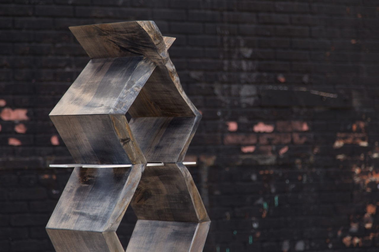 a detail view of the top portion of a SENTIENT contemporary friends bookcase with wood zig zag sides and metal shelves