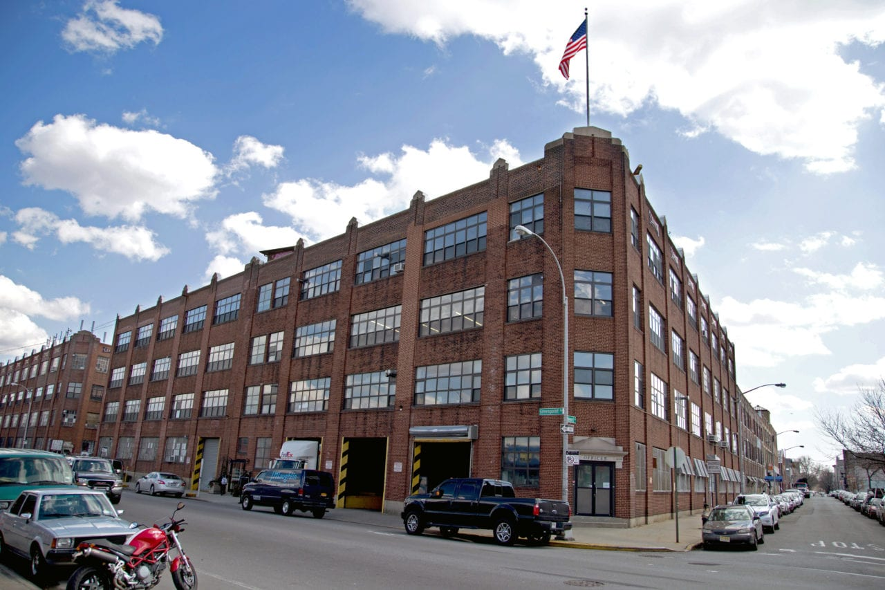 an outside corner street view of SENTIENT red brick office building with American flag waving on top
