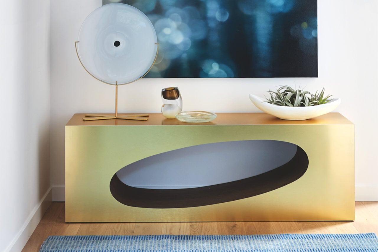 a custom brass SENTIENT contemporary designed Orbit coffee table with oval cutout in luxury walnut with sculpture on top