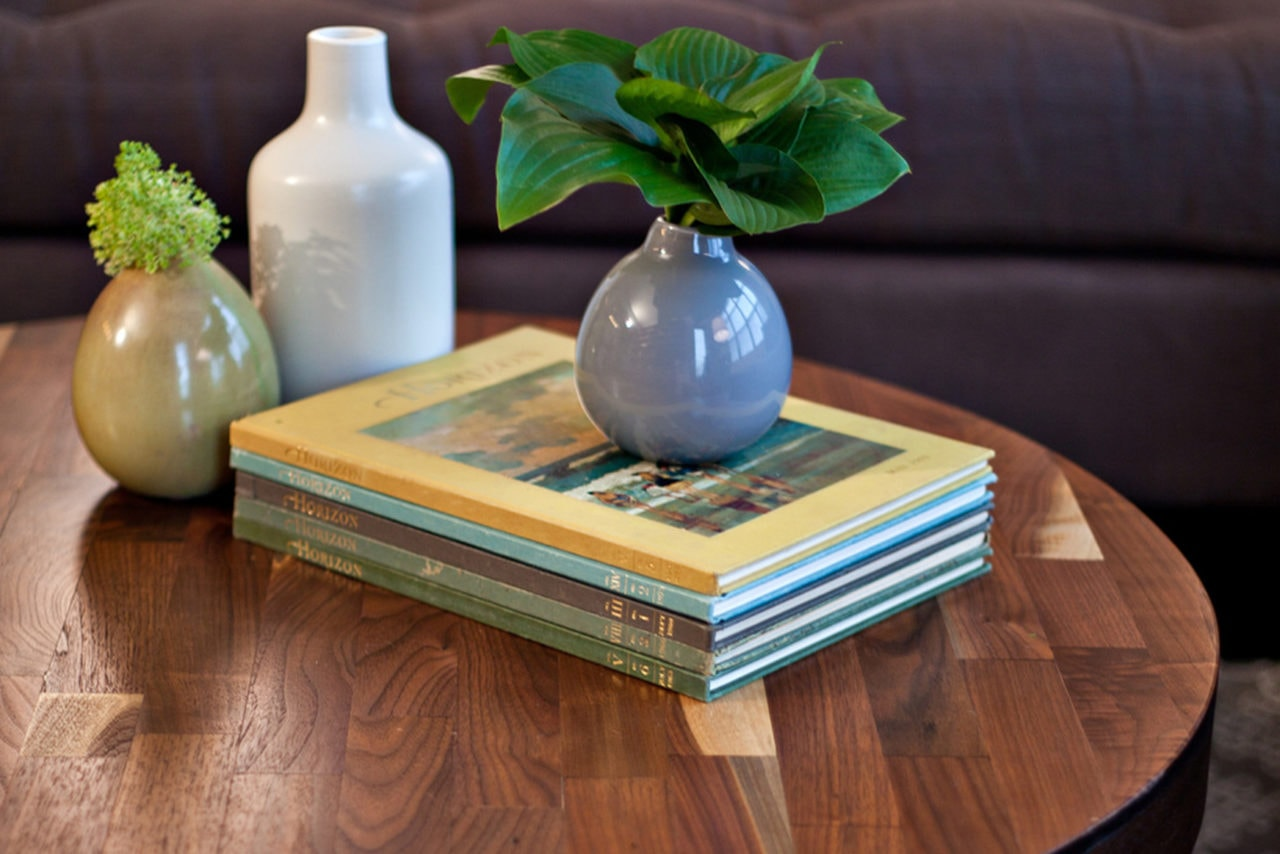 a SENTIENT contemporary designed round custom wood coffee table with stack of books and three luxury ceramic vases