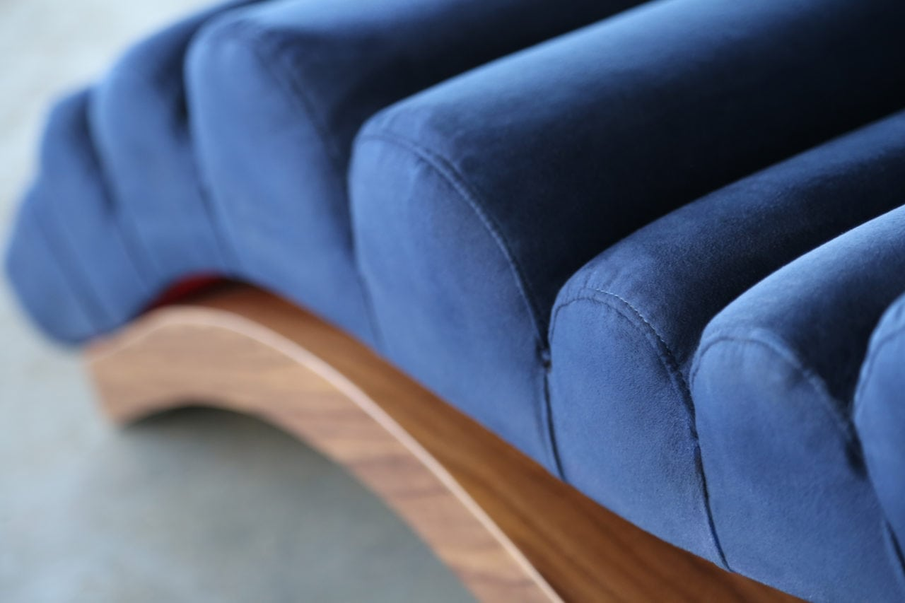 a SENTIENT contemporary designed custom wave lounge chair detail in luxury blue velvet with walnut base