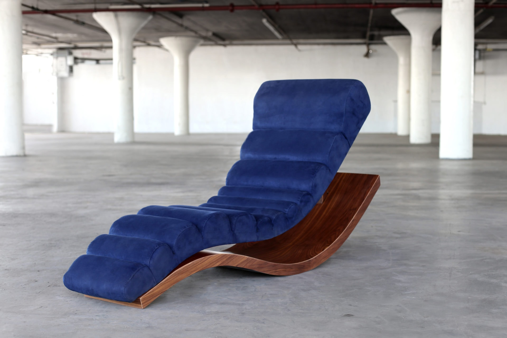 SENTIENT contemporary designed wave lounge chair in luxury blue velvet with custom walnut base frontal side view in open loft