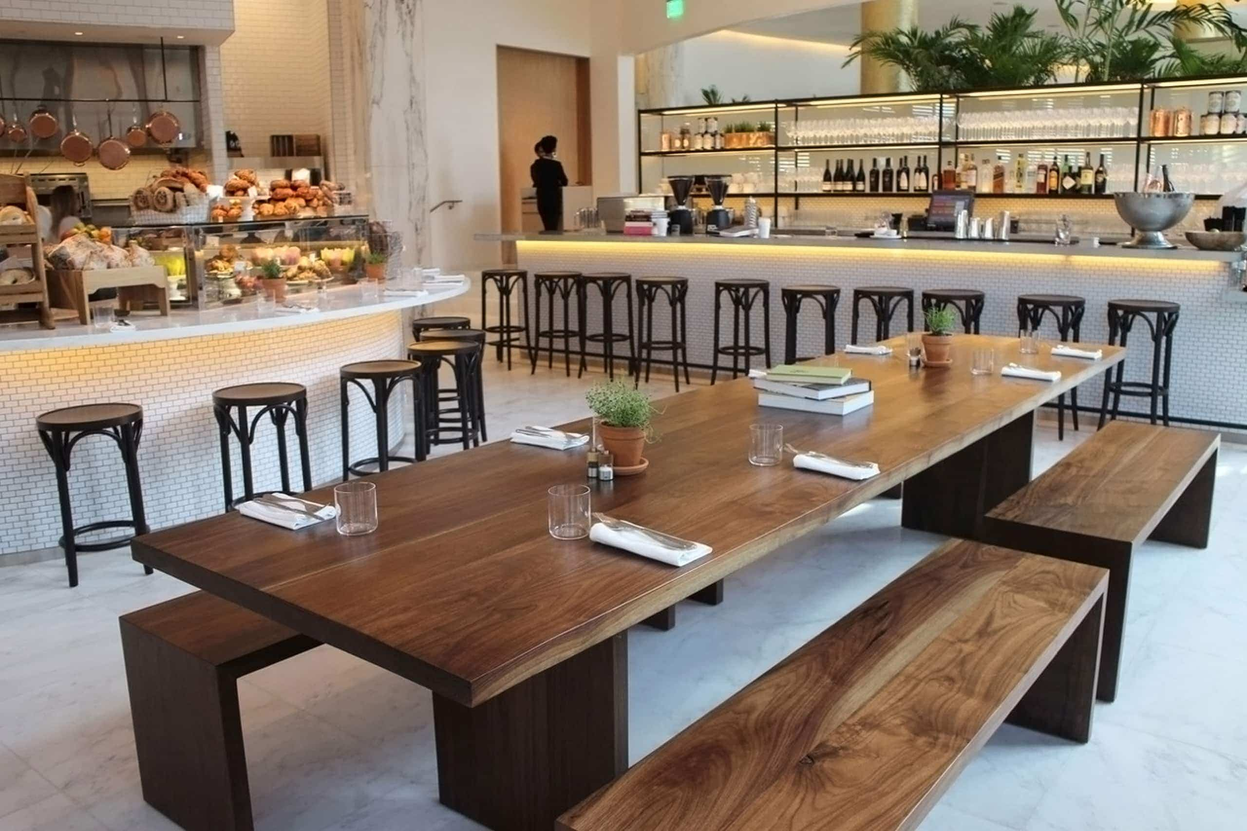 a custom SENTIENT contemporary designed communal walnut table with benches in a luxury Miami edition hotel restaurant