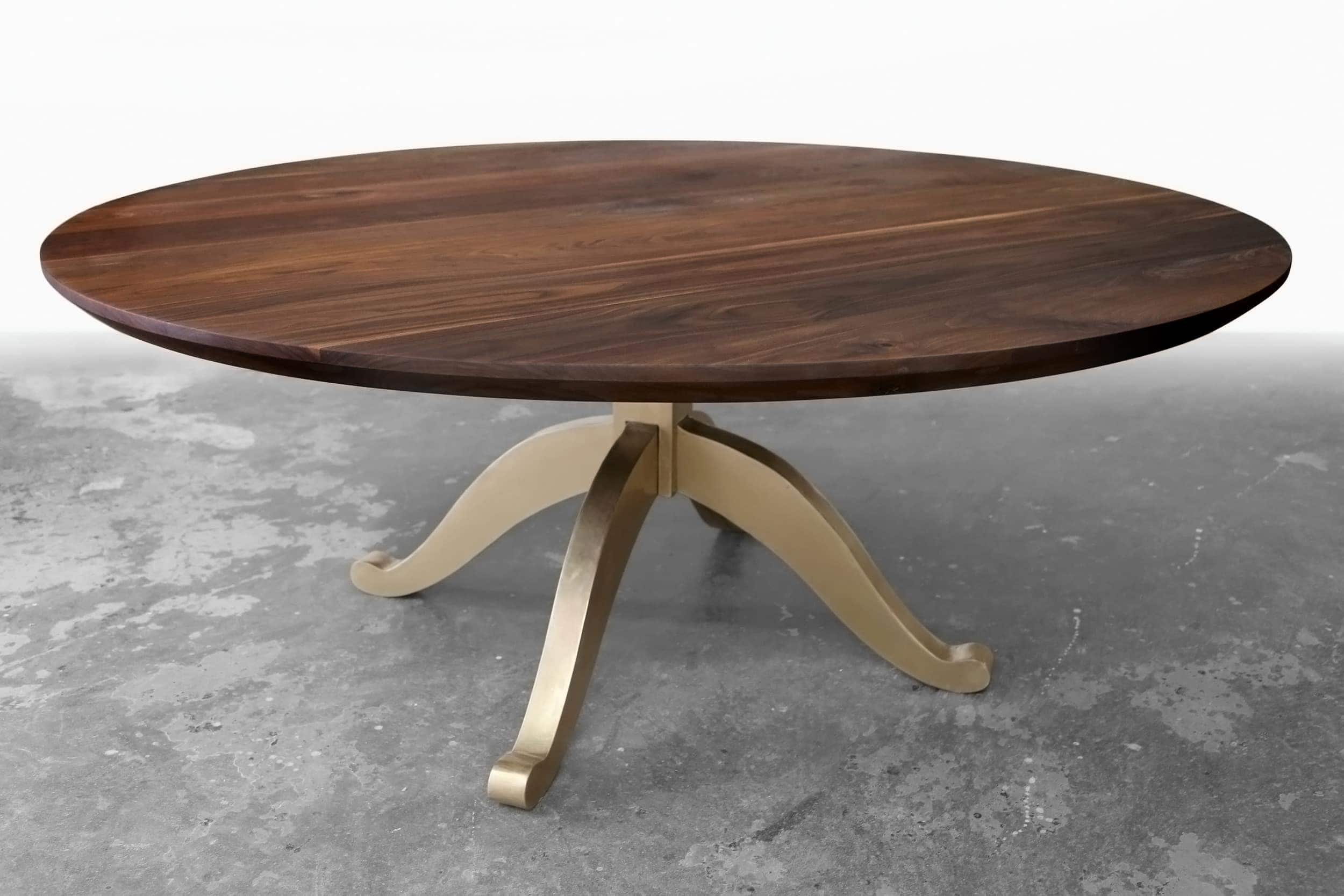 a Sentient round luxury American black walnut contemporary table with brushed brass