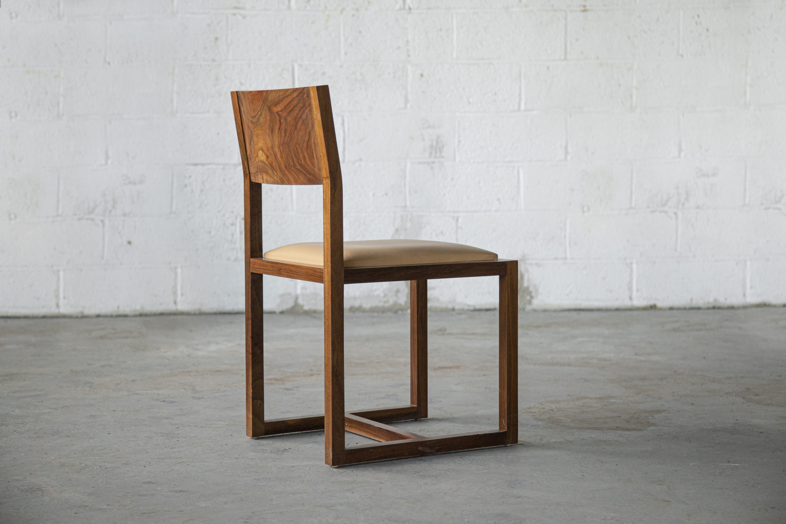 a contemporary designed SENTIENT Saint Lawrence custom dining chair of walnut and luxury leather seat front view